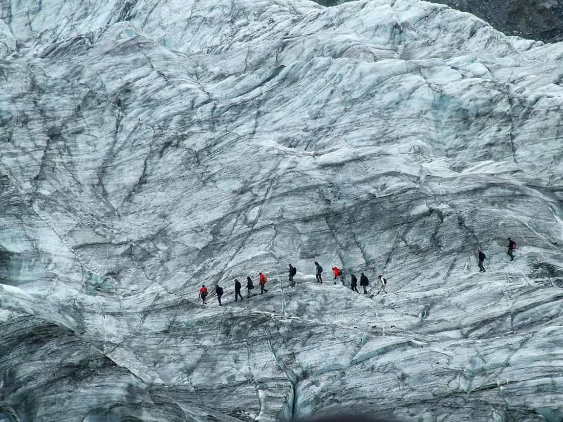 line of people walking along a glacier